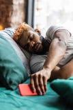 Hombre soñoliento apuesto que oye un sonido del mensaje fotografía de archivo libre de regalías