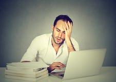 Hombre soñoliento cansado que se sienta en el escritorio con el ordenador portátil de los libros fotos de archivo