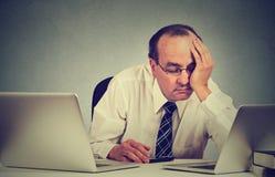 Hombre soñoliento cansado que se sienta en el escritorio con los libros delante de dos ordenadores portátiles fotos de archivo