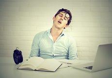 Hombre soñoliento cansado que se sienta en el escritorio con los libros delante del ordenador portátil fotografía de archivo