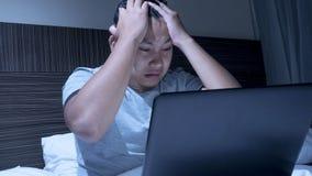 Hombre soñoliento cansado que trabaja en el ordenador portátil hasta medianoche en cama fotos de archivo