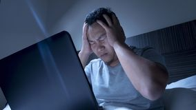 Hombre soñoliento cansado que trabaja en el ordenador portátil hasta medianoche en cama imagen de archivo libre de regalías