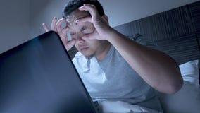 Hombre soñoliento cansado que trabaja en el ordenador portátil hasta medianoche en cama imágenes de archivo libres de regalías