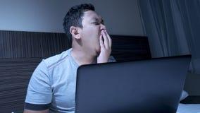 Hombre soñoliento cansado que trabaja en el ordenador portátil hasta medianoche en cama imagen de archivo