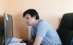 Hombre soñoliento cansado que trabaja en el ordenador Vista lateral fotografía de archivo