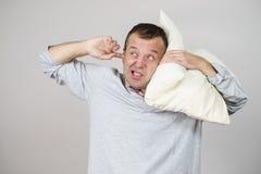 Hombre soñoliento con la almohada que se cierra el oído imágenes de archivo libres de regalías