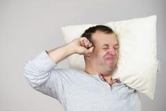 Hombre soñoliento con la almohada que se cierra el oído fotografía de archivo libre de regalías