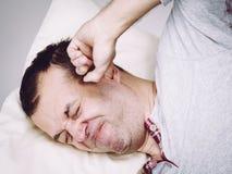 Hombre soñoliento con la almohada que se cierra el oído fotos de archivo libres de regalías