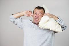 Hombre soñoliento con la almohada que se cierra el oído foto de archivo