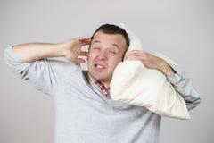 Hombre soñoliento con la almohada que se cierra el oído foto de archivo libre de regalías