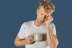 Hombre soñoliento con una taza de bebida caliente El sol se levanta sobre las nubes del mar y del oro fotos de archivo