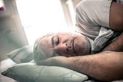 Hombre soñoliento Hombre en cama fotografía de archivo libre de regalías