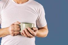 Hombre soñoliento en la camiseta blanca con una taza de café en fondo azul El sol se levanta sobre las nubes del mar y del oro fotos de archivo libres de regalías