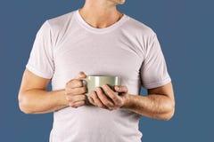 Hombre soñoliento en la camiseta blanca con una taza de café en fondo azul El sol se levanta sobre las nubes del mar y del oro imagen de archivo