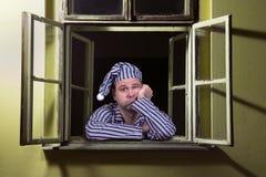 Hombre soñoliento en la ventana Fotografía de archivo libre de regalías