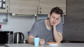 Hombre soñoliento hermoso que desayuna en la tabla imágenes de archivo libres de regalías