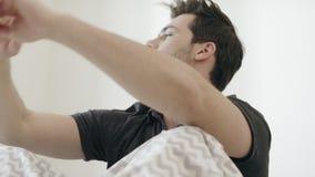Hombre soñoliento que bosteza en cama por mañana Individuo hermoso que estira en dormitorio almacen de metraje de vídeo