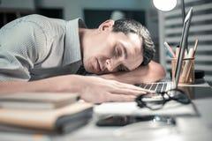 Hombre soñoliento que descansa poniendo su cabeza en la tabla de la oficina fotografía de archivo libre de regalías