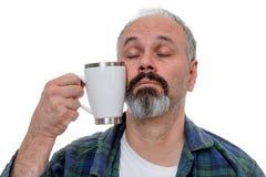 Hombre soñoliento que lucha para beber el café foto de archivo