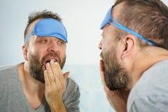 Hombre soñoliento que mira el espejo y que bosteza imagenes de archivo