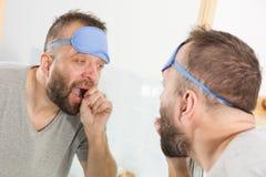 Hombre soñoliento que mira el espejo y que bosteza fotografía de archivo libre de regalías