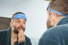 Hombre soñoliento que mira el espejo y que bosteza foto de archivo libre de regalías
