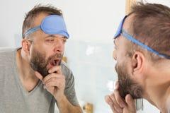 Hombre soñoliento que mira el espejo y que bosteza imagen de archivo