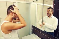 Hombre soñoliento que mira en el espejo imagen de archivo