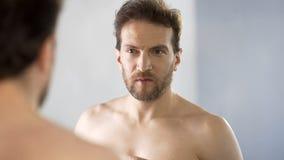 Hombre soñoliento que mira en espejo el cuarto de baño, falta de sueño, insomnio sufridor foto de archivo