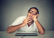 Hombre soñoliento que trabaja en el ordenador que bosteza imagenes de archivo
