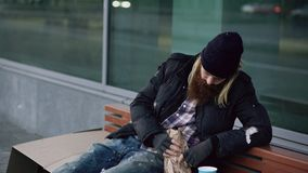 Hombre soñoliento sin hogar borracho que se sienta en banco en la acera imagen de archivo libre de regalías