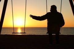 Hombre solamente que falta a su socio en la puesta del sol fotografía de archivo