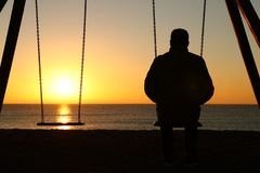 Hombre solamente que mira puesta del sol en la playa fotografía de archivo
