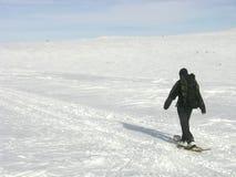 Hombre solitario con un morral snowshoeing Foto de archivo