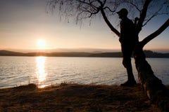 Hombre solitario que mira puesta del sol colorida en la orilla del lago del otoño Árbol de abedul del bramido del soporte del hom Imágenes de archivo libres de regalías