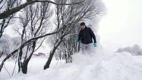Hombre solo, activando a través del bosque del invierno en nieve profunda almacen de video