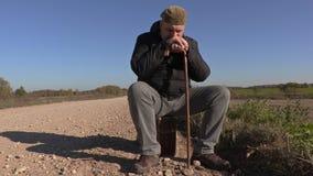 Hombre solo con la muleta que se sienta en la maleta en el camino rural almacen de metraje de vídeo
