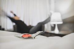 Hombre solo con los condones en cama imagen de archivo