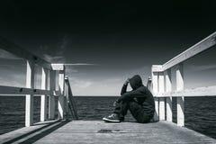 Hombre solo en el borde del embarcadero de madera Fotografía de archivo