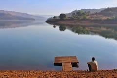 Hombre solo por el río o el lago imagenes de archivo