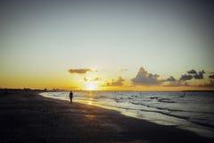 Hombre solo que camina en la playa en la puesta del sol fotos de archivo