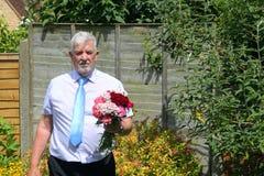 Hombre sombrío con las flores condolencias Imágenes de archivo libres de regalías