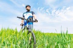 Hombre sonriente adulto joven que se coloca con la bicicleta en la cebada verde fi foto de archivo libre de regalías