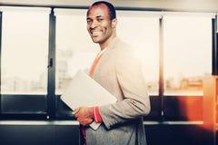 Hombre sonriente agraciado que sostiene el cuaderno imagen de archivo libre de regalías