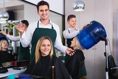 Hombre sonriente alegre que corta el pelo largo de la muchacha Foto de archivo
