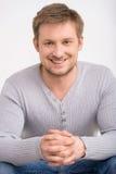 Hombre sonriente atractivo que se relaja en el fondo blanco Imagenes de archivo