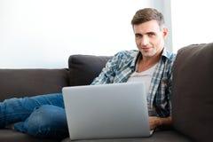 Hombre sonriente atractivo que se sienta en el sofá y que usa el ordenador portátil Foto de archivo libre de regalías