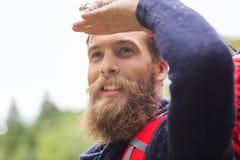 Hombre sonriente con caminar de la barba y de la mochila Imagenes de archivo