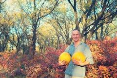 Hombre sonriente con dos calabazas grandes Imagen de archivo libre de regalías