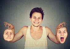Hombre sonriente con dos diversas máscaras de la emoción Fotografía de archivo